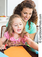Cheerful little girl doing arts and crafts with mother at the table at home in kitchen