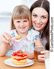 Cheerful little girl eating waffles with strawberries in the kitchen