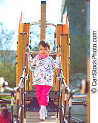 Cheerful little girl having fun at the playground