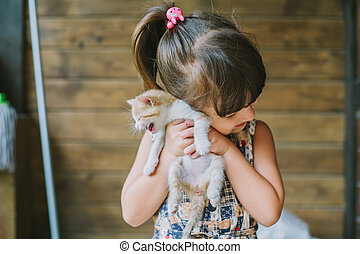 cheerful little girl holding a frightened cat in hands