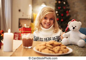 Cheerful little girl holding present and candy cane sitting at wooden table, looking at camera