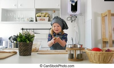 Cheerful little girl in apron rolls out the dough in the kitchen