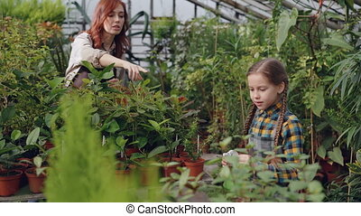 Cheerful little girl is spraying water on pot flowers while her mother is working in greenhouse and talking to her. Family business, farming and childhood concept.