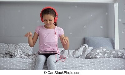 Cheerful little girl listening to music