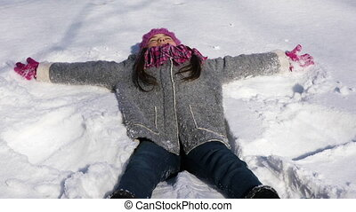 Cheerful little girl making snow angel