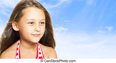 cheerful little girl on a background of blue sky