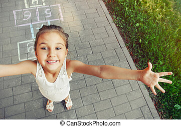 cheerful little girl playing hopscotch on playground outside...