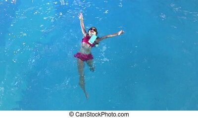 Cheerful little girl playing under water in pool.