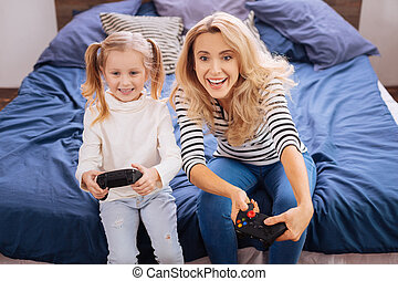 Cheerful little girl playing with her mummy