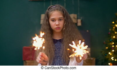 Cheerful little girl playing with sparklers at xmas -...
