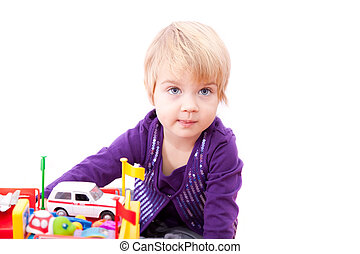 Cheerful little girl playing with toys