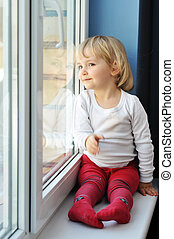 girl sits at window - cheerful little girl sits at window ...