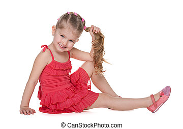 Cheerful little girl sits on the floor