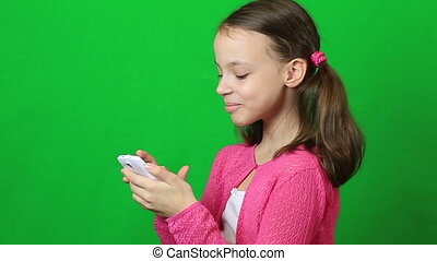 Cheerful little girl with a smartphone in hand.