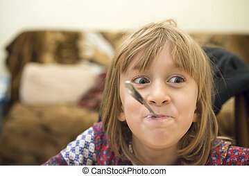 Cheerful little girl with a spoon in her mouth