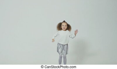 Cheerful little girl with the unusual hairstyle jumping in slow motion