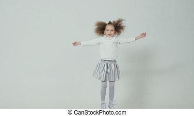 Cheerful little girl with the unusual hairstyle jumping in...