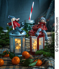 Cheerful little men in red clothes sit on burning lanterns. Checkered plaid and tangerines with leaves surrounded by fir branches.