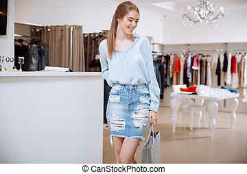 Cheerful lovely young woman doing shopping in clothing store