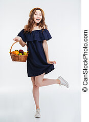 Cheerful lovely young woman in hat holding basket with fruits