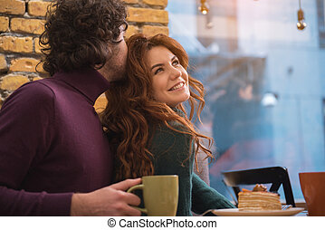 Cheerful lovers having romantic date in cafe