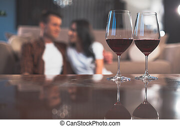 Cheerful lovers having romantic evening with elegant beverage