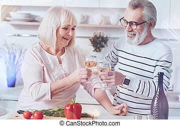 Cheerful loving aged couple drinking white wine