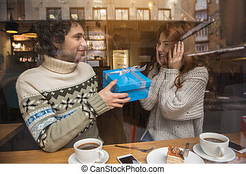 Cheerful loving couple celebrating holiday in cafe