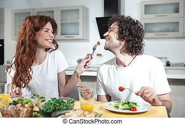 Cheerful loving couple eating healthy food in kitchen