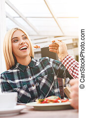 Cheerful loving couple is dating in restaurant