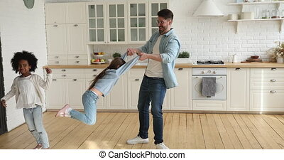 Cheerful loving dad playing with mixed ethnicity kids in ...
