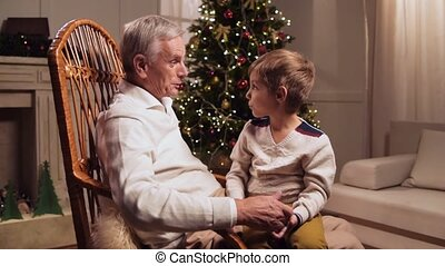Cheerful loving elderly man presenting his grandson a Christmas present