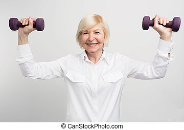 Cheerful madam is exercising with light weights. She does that because she has a careless retirement and much time to do that. Isolated on white background.