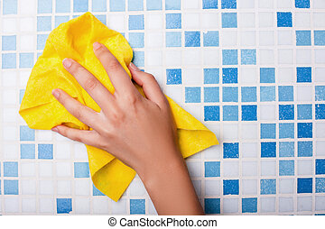 Cheerful maid is cleaning tiled surface with a wisp