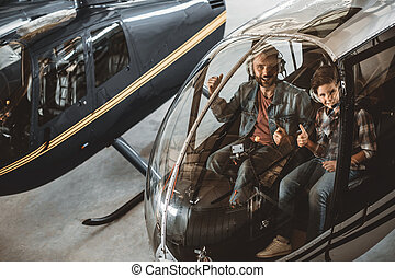 Cheerful male and boy in rotor plane