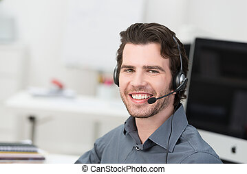 Cheerful male call centre operator or businessman wearing a...