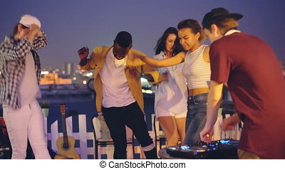 Cheerful male deejay is working with mixing console and dancing while multi-ethnic group of friends Caucasian and African American are having fun at rooftop party.
