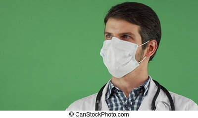 Cheerful male doctor in a medical mask smiling to the camera...