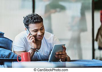 Cheerful male freelancer using modern technology