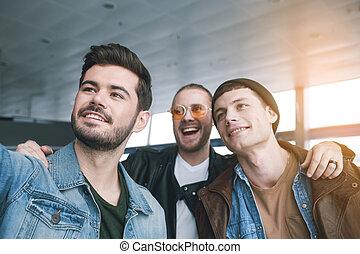 Cheerful male friends taking selfie