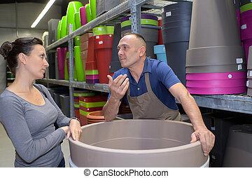 cheerful male gardener advising female customer on pots