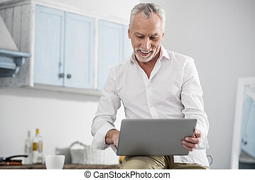 Cheerful male person working at home