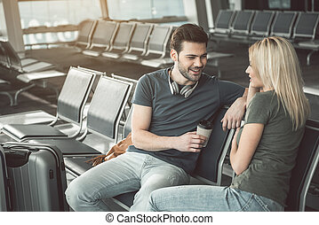 Cheerful male speaking with positive woman in airport