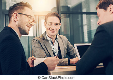 Cheerful male telling with happy colleagues