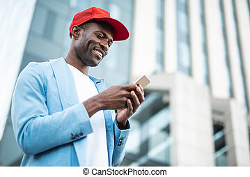 Cheerful male typing in phone