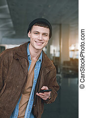 Cheerful male using phone in hall