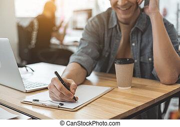 Cheerful male writing in sketchbook