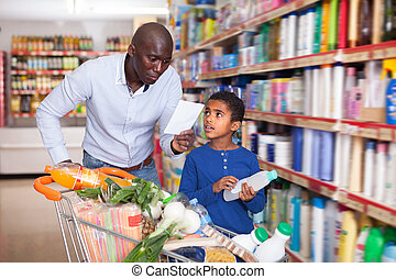 Cheerful man and boy reading shopping list