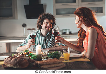 Cheerful man and woman drinking wine in kitchen