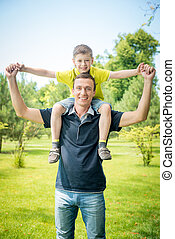 Cheerful man carrying his son on back against park